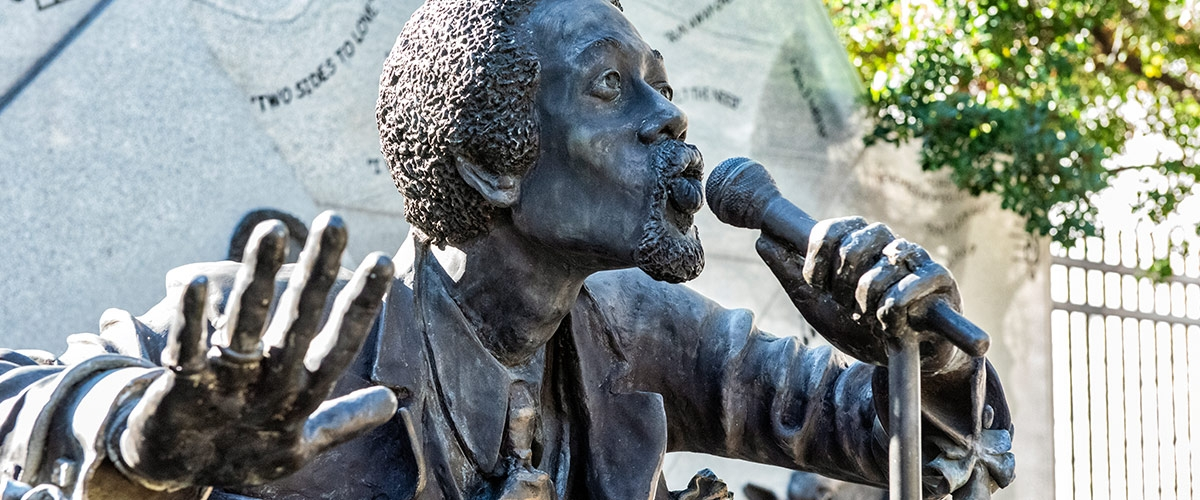Statue of man singing into microphone